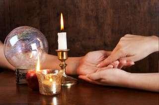 immagine che mostra una lettura della mano con candele accese e sfera di cristallo