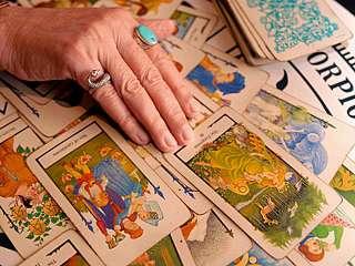 immagine che ritrae la mano di un'operatrice esoterica su le carte dei tarocchi