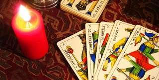 immagine che rappresenta una candela accesa con a fianco carte napoletane su panno rosso