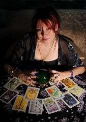 immagine che ritrae una cartomante con le mani su una sfera di cristallo verde e le carte degli arcani disposte davanti a se
