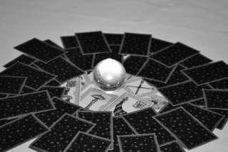 immagine in bianco e nero che ritrae le carte dei tarocchi rivolte a faccia sotto e disposte a cerchio con sfera di cristallo al centro