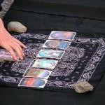 immagine che ritrae sei carte dei tarocchi disposte in fila orizzontale sopra un panno nero con decorazioni bianche