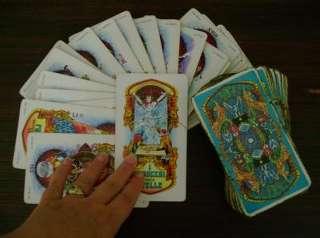 immagine di una mano di un operatrice esoterica appoggiata sopra carte disposte su sfondo scuro