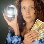 immagine che ritrae una cartomante con le braccia incrociate che tiene tra le mani una sfera di cristallo e tre carte dei tarocchi