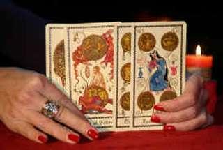 immagine di mani con unghie smaltate di rosso di una operatrice esoterica che tiene in mano i tarocchi napoletani