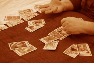 immagine che ritrae alcune carte disposte su un tavolo e le mani di un cartomante
