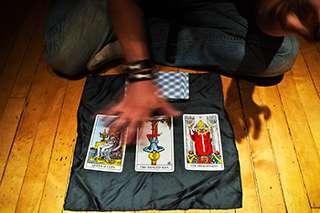 immagine che ritrae le gambe incrociate di un cartomante che passa la mano destra sopra carte dei tarocchi disposte su un telo nero