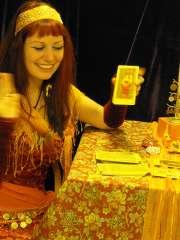 immagine di un'operatrice esoterica sorridente che mostra una carta dei tarocchi tra quelle disposte sul tavolo