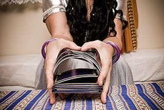 primo piano delle mani di una cartomante che mischia le carte