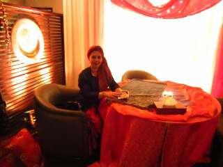 immagine che ritrae una cartomante seduta su una poltrona ad un tavolo rotondo con lunga tovaglia rossa