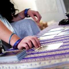 mani di una cartomante che sceglie una carta tra quelle disposte sul panno a righe viola di fronte a se