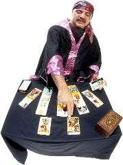 immagine che ritrae un cartomante che indossa una tunica nera ed indica una carta specifica tra quelle disposte sul tavolo