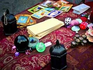 immagine che ritrae alcune carte dei tarocchi e diversi amuleti disposti su un tavolo