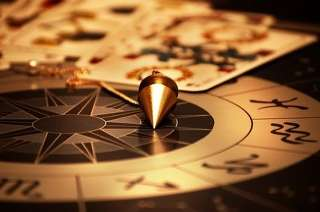 immagine che ritrae un pendolo ed alcune carte dei tarocchi disposte su una tavola astrologica