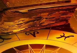 immagine che rappresenta un libro molto antico disposto sopra tavola dei segni zodiacali