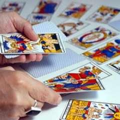 immagine delle mani di un operatrice esoterica con alcune carte degli arcani
