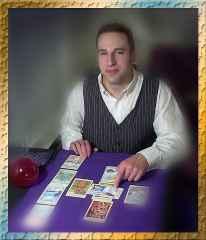 immagine che ritrae un operatore esoterico che indica una carta tra quelle disposte su un panno viola di fronte a se