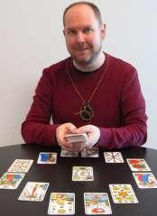 immagine che ritrae un cartomante con un mazzo di carte in mano ed altre disposte davanti a se