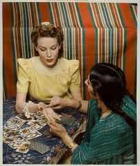 immagine di una cartomante che legge le linee della mano alla sua consultante
