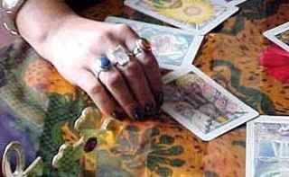 mano di cartomante che porta alle dita diversi anelli appoggiata su un tavolo in cui sono stese carte dei tarocchi