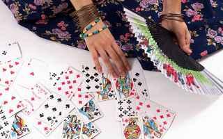 immagine che ritrae le mani di un operatrice esoterica con ventaglio aperto e numerose carte dei tarocchi