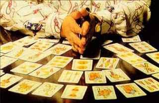 immagine che ritrae le mani di un cartomante circondate da numerose carte degli arcani disposte su più file