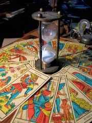 immagine che ritrae numerose carte dei tarocchi disposte in modo circolare con al centro una clessidra