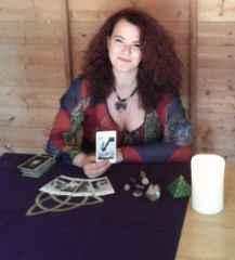 immagine di un'operatrice esoterica che tiene in mano una carta dei tarocchi