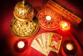 immagine di un tavolo ricoperto da un panno rosso su cui sono disposte alcune carte e delle candele accese