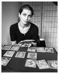 immagine in bianco e nero di un'operatrice esoterica con in mano il mazzo dei tarocchi e varie carte disposte davanti a lei su un tavolo scuro