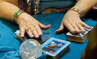 immagine che ritrae le mani di una cartomante posate su due mazzi di carte