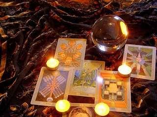 immagine che ritrae carte degli arcani con delle piccole candele accese e una sfera in cristallo