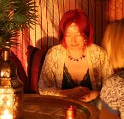 immagine di una cartomante che osserva tre arcani disposti su un tavolo rotondo