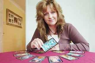 immagine di una cartomante che mostra una tra le carte disposte di fronte a se