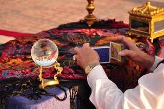 immagine che ritrae le mani di un cartomante uomo mentre mischia le carte e ha alla sua sinistra una sfera di cristallo