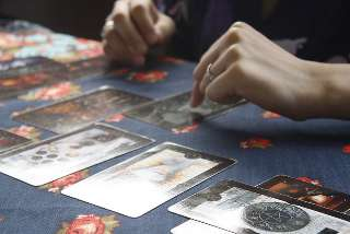 immagine di mani di una cartomante che indicano una carta tra quelle disposte sul tavolo