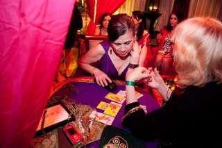immagine di un'operatrice esoterica che legge le carte disposte un un panno viola alla sua consultante