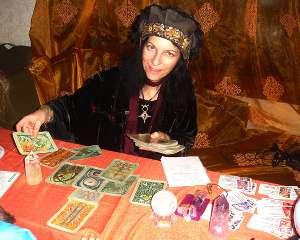 immagine che ritrae un'operatrice esoterica che tiene in una mano alcune carte degli arcani e nell'altra il tarocco che sta interpretando