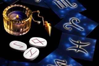 immagine che ritrae alcuni simboli dei segni zodiacali con nel mezzo una candela ed in pendolino