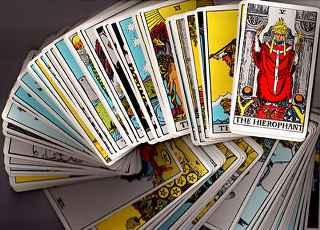 immagine che ritrae molteplici carte dei tarocchi distribuite su un tavolo e la carta del Papa in primo piano