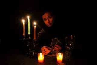 immagine di una cartomante su sfondo completamente nero con candele accese di fronte e al suo fianco