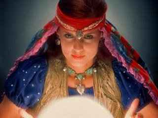 immagine che ritrae una cartomante con un velo colorato che le cinge la testa e un pendente sulla fronte mentre consulta la sfera di cristallo