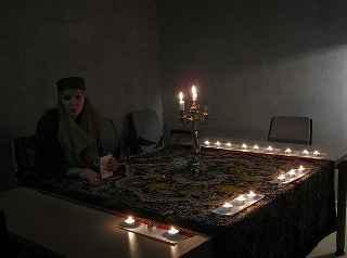 immagine che ritrae una cartomante seduta ad un tavolo circondata da numerose candele accese