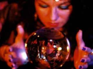 immagine che ritrae un operatrice esoterica con la sfera di cristallo tra le mani