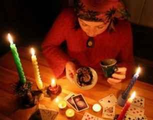 immagine che ritrae una cartomante mentre legge i fondi del caffè con diverse candele accese e carte dei tarocchi