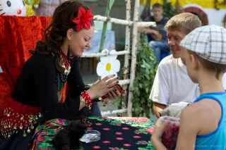 immagine che ritrae un operatrice esoterica con un fiore rosso tra i capelli che legge le carte