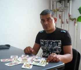 immagine che ritrae un cartomante seduto ad un tavolo su cui sono distribuite le carte dei tarocchi
