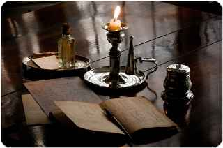 immagine che ritrae una candela accesa nel suo portacandela