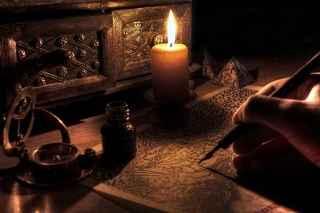 immagine che ritrae una candela accesa e la mano di un operatore esoterico che tiene una penna