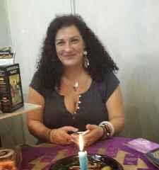 immagine che ritrae una cartomante sorridente con alcune carte in mano ed una candela accesa di fronte